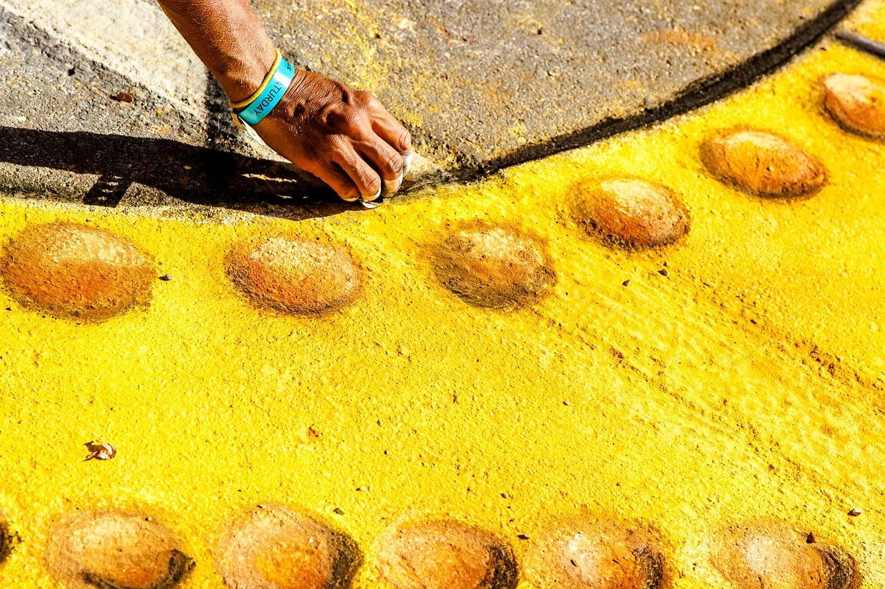 Child playing with yellow sidewalk chalk.